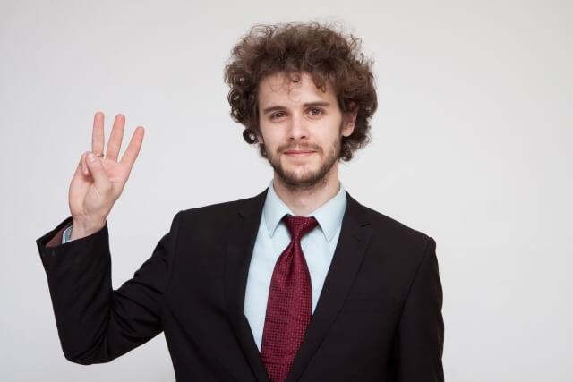 3本の指を立てる男性
