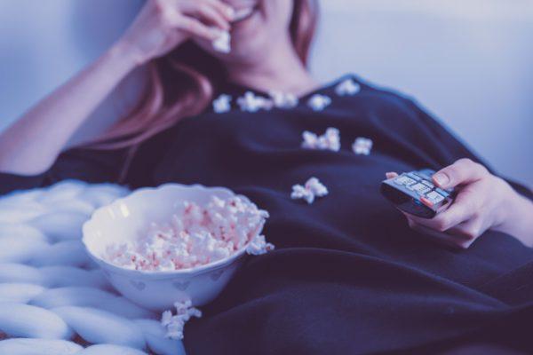 ポップコーンを食べながら映画を見る女性