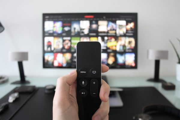 リモコンを持つ手とテレビ